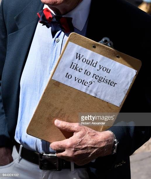 A man with a clipboard registers voters at a rally in Santa Fe New Mexico