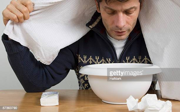 A man with a cold breathing steam from a bowl