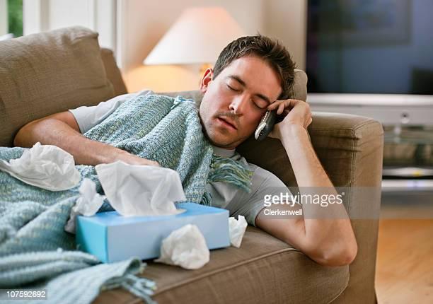 Mann mit einem kalten Entspannung in sofa holding Gewebe und