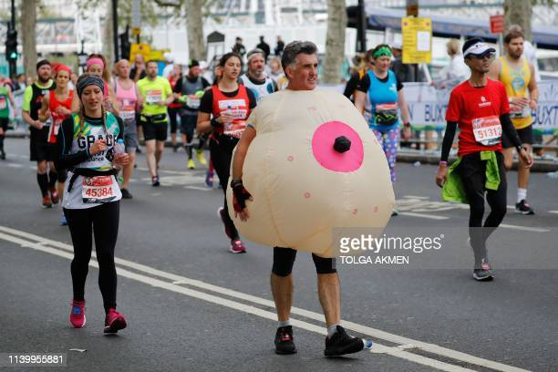 TOPSHOT A man with a costume runs as he competes in the 2019 London Marathon in central London on April 28 2019 / Restricted to editorial use...
