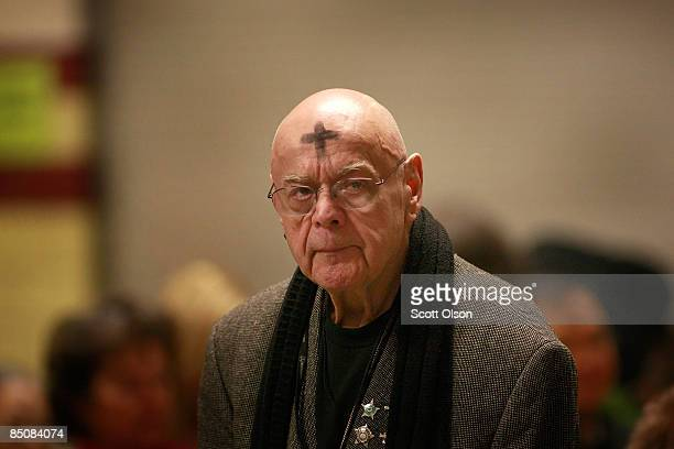 A man with a cross of ashes on his forehead paticipates in an Ash Wednesday mass in the cafeteria of Holy Name Cathedral February 25 2009 in Chicago...