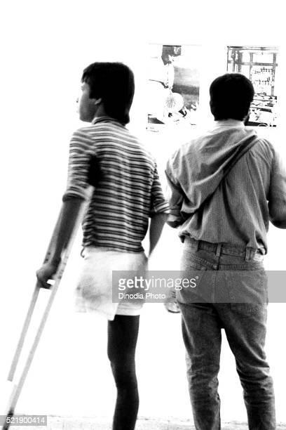 Man with a crutch at photography exhibition, Mumbai, Maharashtra, India, Asia, 1986