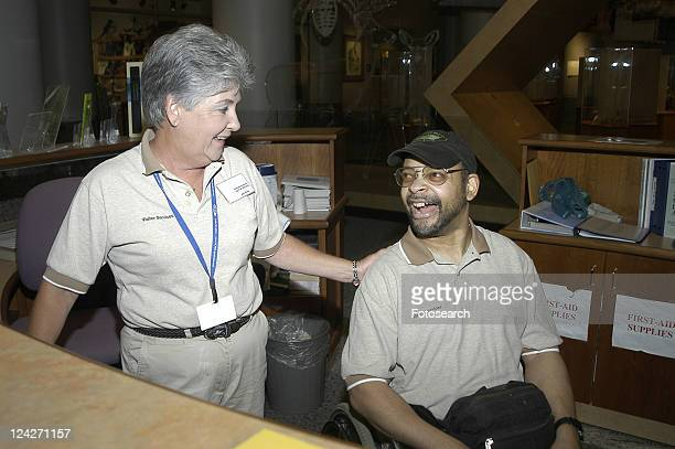 man with a disability laughing with a coworker while working as a receptionist at a museum. - cerebrum stock pictures, royalty-free photos & images