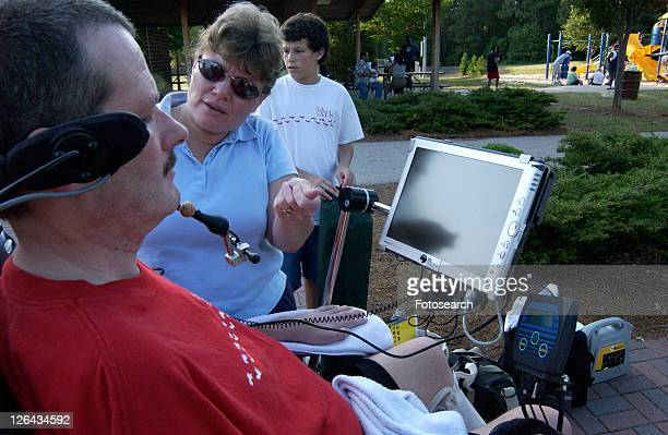 man with a disability talking with a woman via his mouth powered communication system. - quadriplegic fotografías e imágenes de stock
