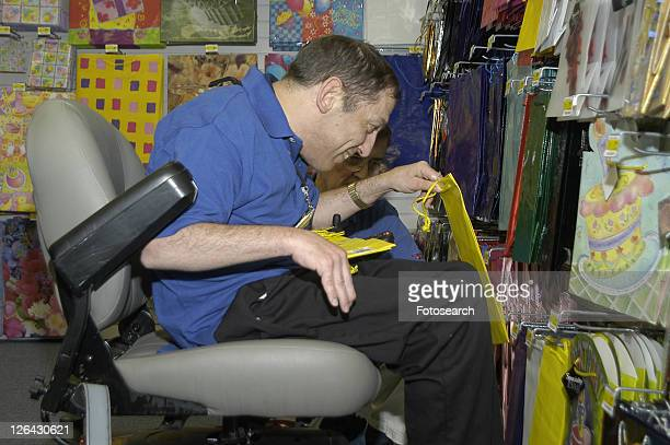 man with a disability using a wheelchair for mobility, working in a store. - cerebrum stock pictures, royalty-free photos & images