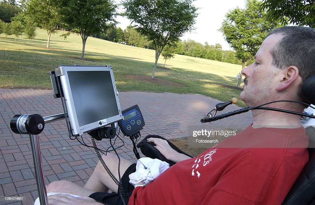 Man with a disability utilizing a mouthpiece to give commands to communications system that allows him to communicate. : Stock Photo