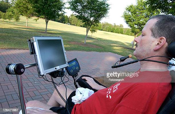 man with a disability utilizing a mouthpiece to give commands to communications system that allows him to communicate. - quadriplegic fotografías e imágenes de stock