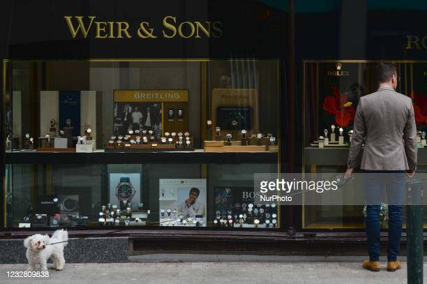 Man with a dog looks ar Weir and Son jewelry shop window, on Grafton Street in Dublin. After five months of strict lockdown, the first stage of...