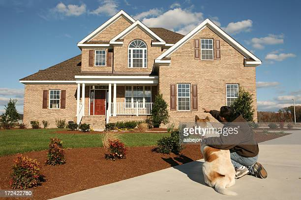 A man with a dog pointing at a house