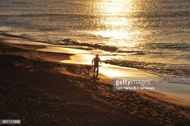 A man with a dog running on morning beach in Kamakura city in Kanagawa prefecture in Japan