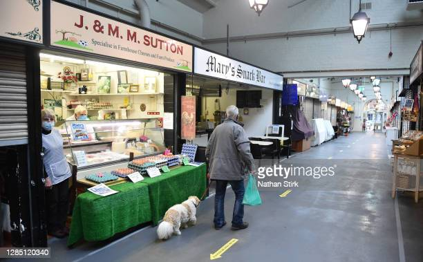 Man with a dog shops in Leek Market on November 11, 2020 in Leek, England. The Booksellers Association has called on the government to classify...
