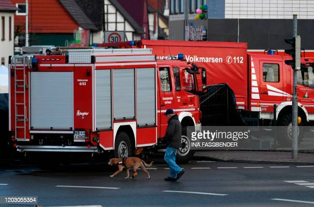 A man with a dog walks past firefighting vehicles at the site where a man who drove into a carnival procession on February 25 2020 in Volkmarsen near...