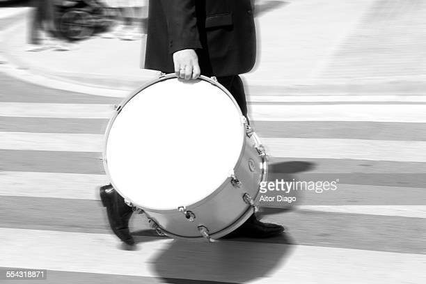 Man with a drum walking on a zebra crossing.
