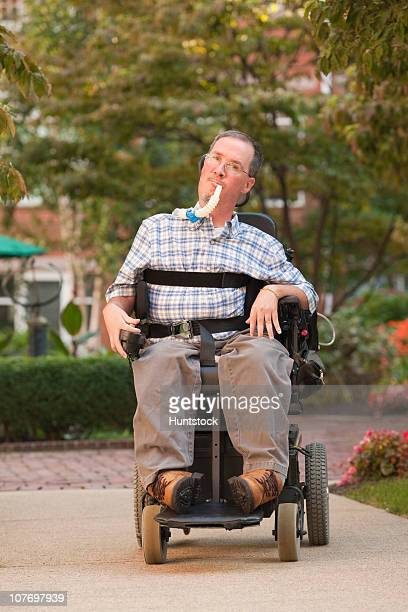 man with a duchenne muscular dystrophy sitting in a wheelchair - duchenne muscular dystrophy stock photos and pictures