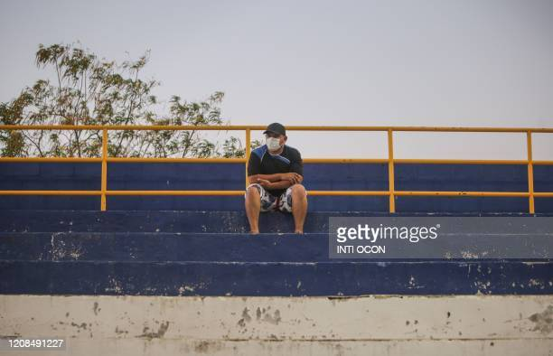 Man with a face mask as a precautionary measure against the spread of the new coronavirus, COVID-19, watches the football match between Managua FC...