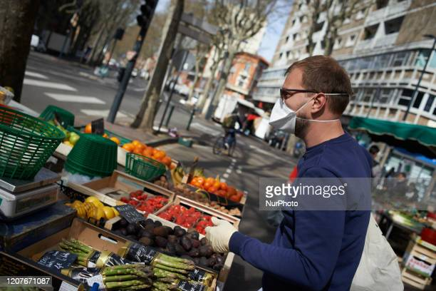 A man with a face mask buys fruits and vegetables on the main open air market in Toulouse France on March 19 2020 For the 3rd day French people are...
