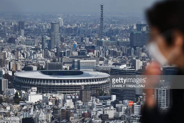 TOPSHOT A man with a face mask look out at the New Tokyo Stadium the main venue for the 2020 Olympic Games from a viewing area in Tokyo on March 9...