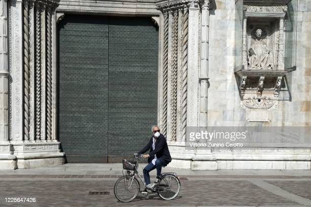 Man with a face mask rides a bicycle on May 18, 2020 in Como, Italy. Restaurants, bars, cafes, hairdressers and other shops have reopened, subject to...