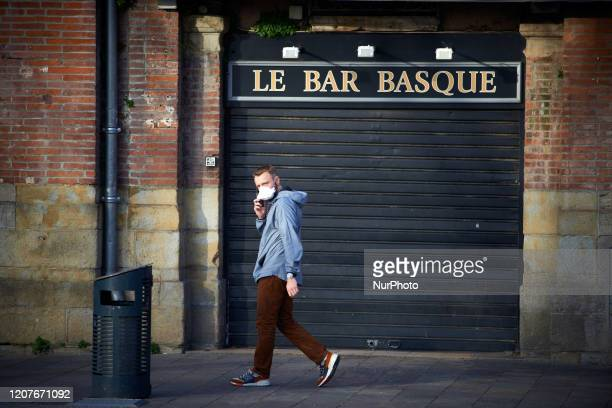 A man with a face mask walks near a closed bar in Toulouse France on March 19 2020 For the 3rd day French people are on lockdown Since March 16t when...