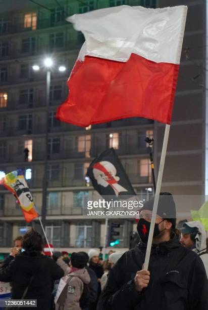 """Man with a face mask with a lightning bolt on it as a sign of """"Strajk Kobiet"""" attends a demonstration demanding the restoring of the right to..."""