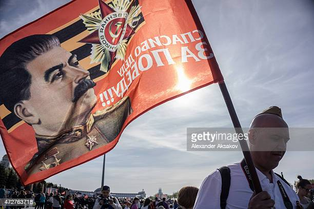 A man with a flag with a portrait of Stalin in Victory Park during celebrations marking the 70th anniversary of the victory over Nazi Germany and the...