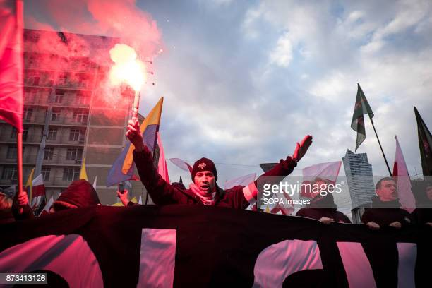Man with a flare on his hand and the nazi salute during the annual nationalist march of Poland´s Independency Day Poland's Independence Day is a...