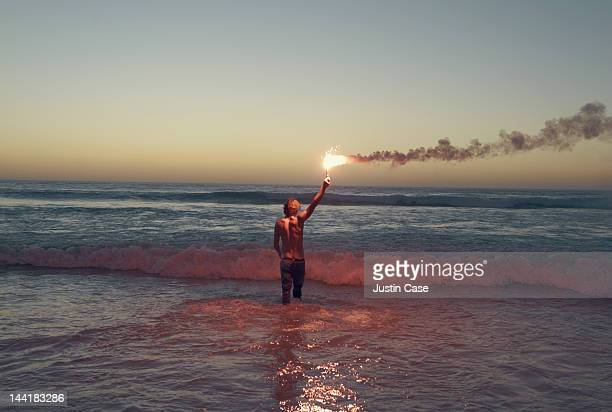 man with a flare walking out into the ocean