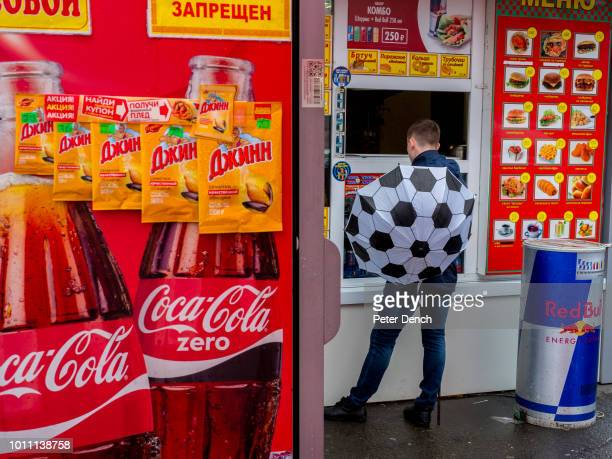 A man with a football themed umbrella in the centre of Vladivostok a major Pacific port city in Russia overlooking Golden Horn Bay near the borders...