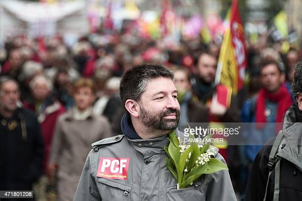 A man with a French Communist Party sticker and lily in his pocket attends a May Day rally on May 1 2015 in Rennes AFP PHOTO / DAMIEN MEYER