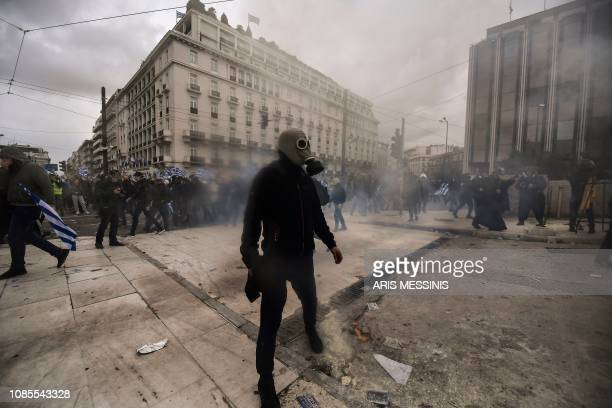 TOPSHOT A man with a gas mask stands as protesters clash with riot police near the Greek Parliament in Athens on January 20 2019 during a...