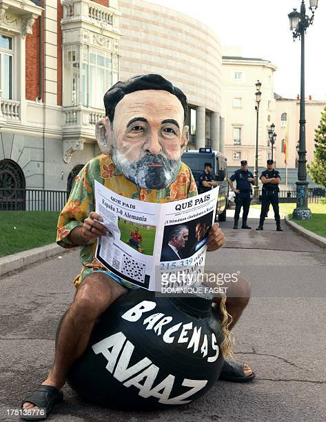 A man with a giant homemade head representing Spanish Prime Minister and PP leader Mariano Rajoy holds a fake newspaper reading 'Truth of...