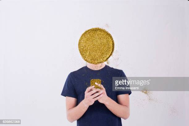 Man with a gold head holding a gold phone