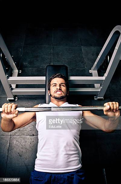 A man with a gray cutoff bench pressing