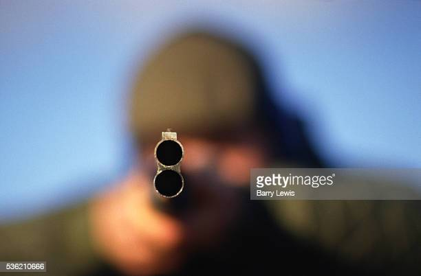 A man with a green hunting jacket a flat tweed farmers cap and blue ear protectors stands in a muddy field taking aim with a doublebarrel shotgun He...