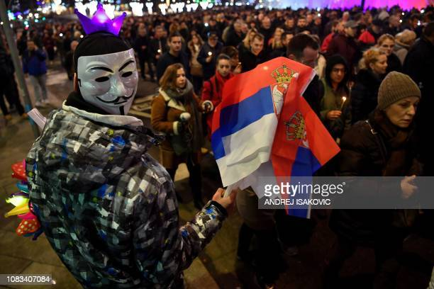 A man with a Guy Fawkes mask sells Serbian national flags during a silent march in Belgrade in memory of Serb politician Oliver Ivanovic murdered a...