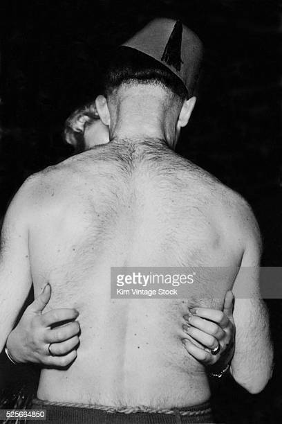 A man with a hairy back and wearing a fez kisses a woman with her long finger nails impaling his skin