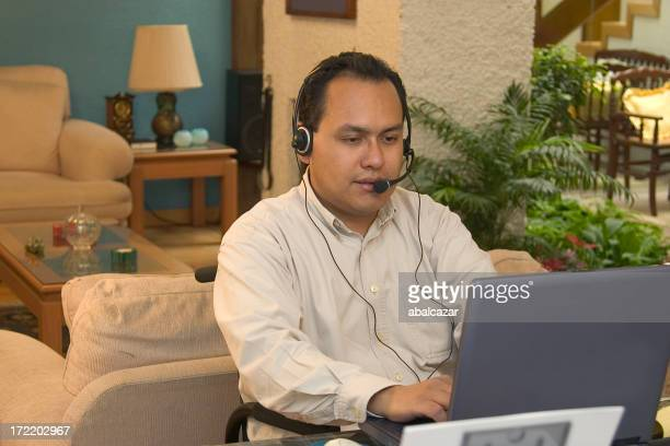 Man with a headset using a laptop at home