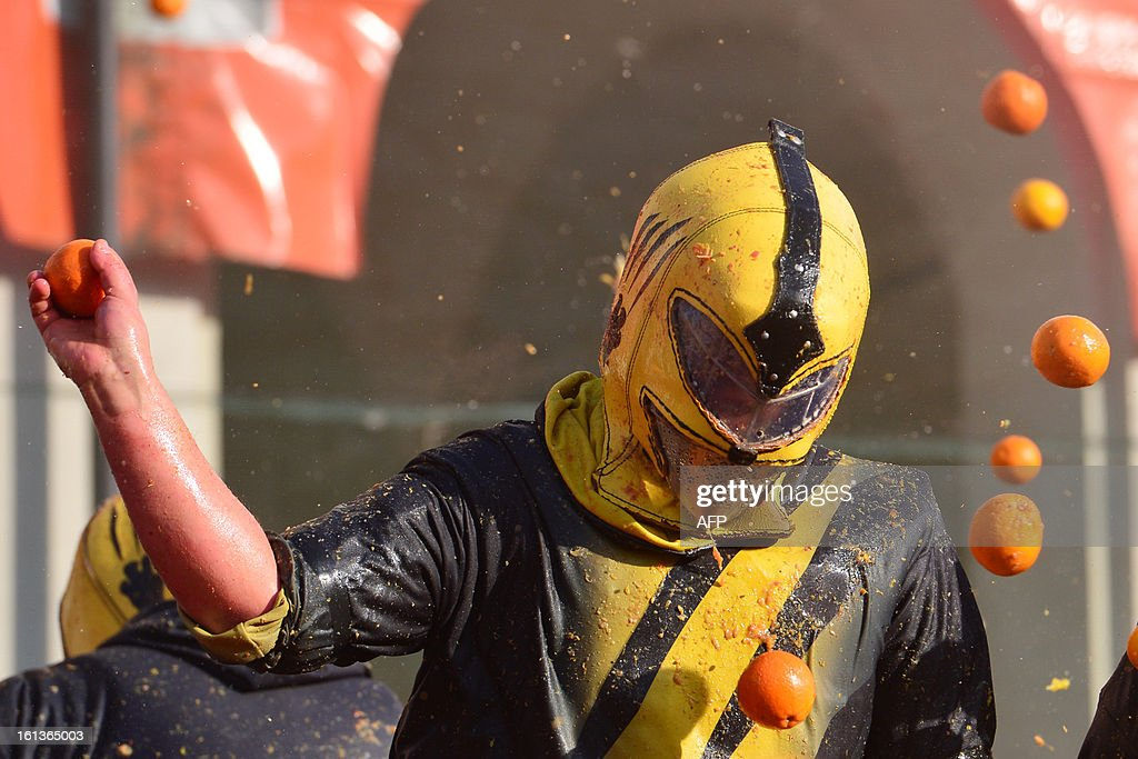 A man with a helmet throws an orange while being hit by oranges during the traditional 'battle of the oranges' held during the carnival in Ivrea, near Turin, on February 10, 2013. During the event which marks the people's rebellion against tyrannical lords who ruled the town in the Middle Ages, revellers parading on floats represent guards of the tyrant, while those on foot the townsfolk.