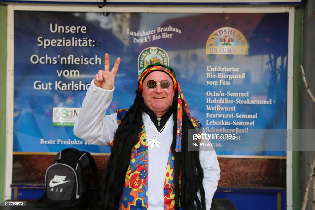 A man with a hippie costume showing the peace sign is seen in the Munich Carnival, in Munich, Germany, on 13 February, 2018.