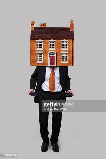 man with a house on his head, emptying his pockets