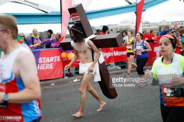 TOPSHOT A man with a Jesusthemed costume runs across Tower Bridge as he competes in the 2019 London Marathon in central London on April 28 2019 /...