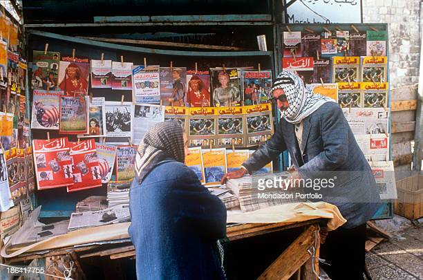 A man with a keffiyeh around his head and a cigarette in his mouth watching a newspaper in an Arabian newspaper kiosk close to the Damascus Gate in...