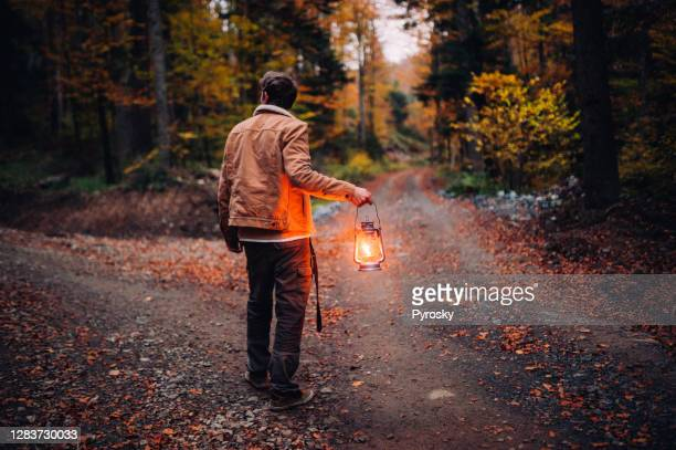 a man with a lantern at a crossroads in the woods - lantern stock pictures, royalty-free photos & images