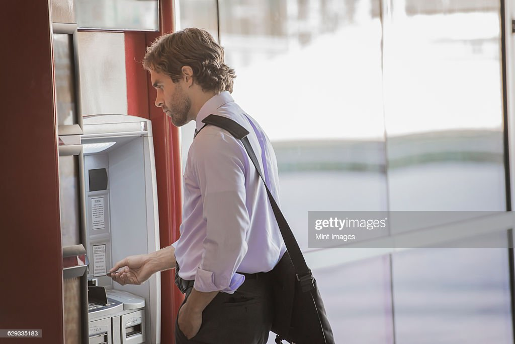 A man with a laptop bag using an ATM, a cash machine on a city street.  : Stock Photo