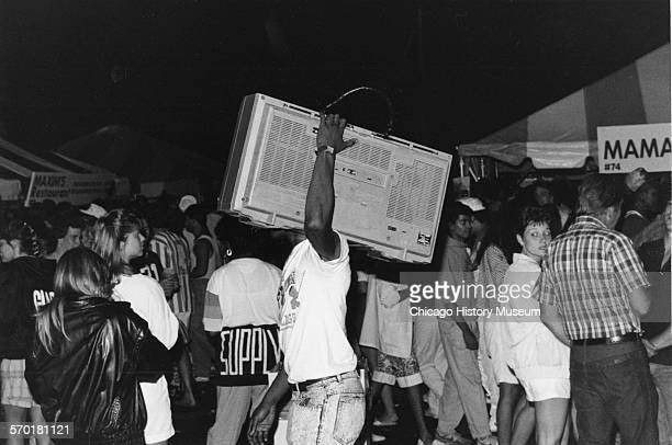 Man with a large radio boom box walking among a crowd at the Taste of Chicago festival at night on Columbus Drive at Congress Parkway Chicago...