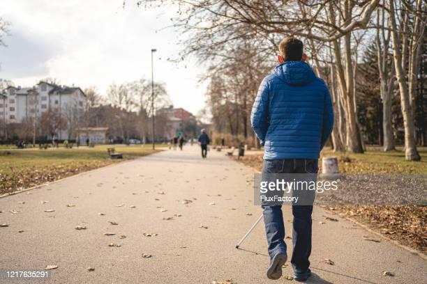 公共の公園で朝の散歩を楽しむ失われた視力を持つ男 - 白杖 ストックフォトと画像