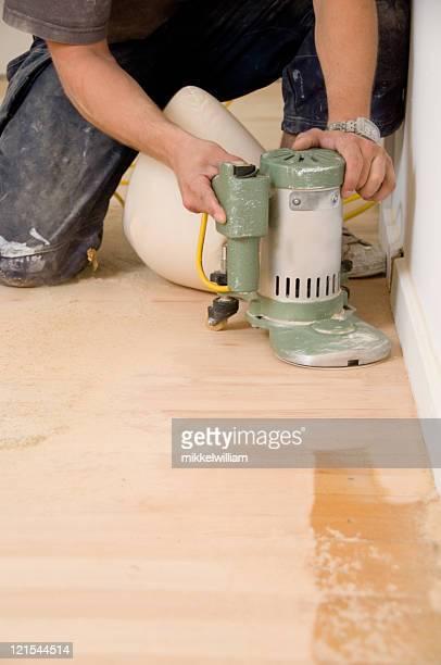 Man with a machine restores hardwood floor
