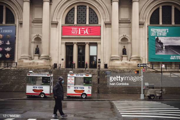 a man with a mask crosses in front of a closed metropolitan museum of art during the outbreak of the coronavirus disease (covid-19) in new york city. - met art gallery photos et images de collection