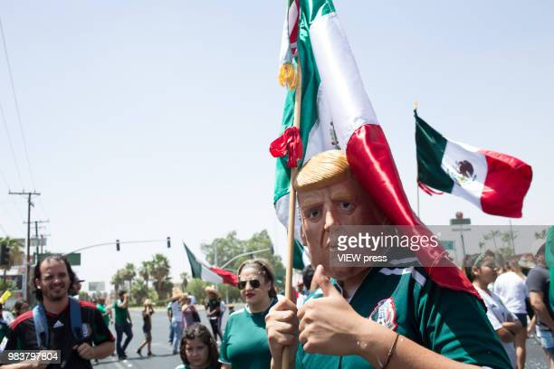 A man with a mask of Donald Trump celebrates Mexico after winning their FIFA World Cup Group F South Korea vs Mexico match on June 23 2018 in...