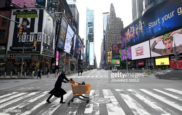 A man with a mask pushes a cart with a sign reading corpse cartte at Times Square in Manhattan on March 17 2020 in New York City The coronavirus...